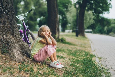 side view of pensive kid resting near bicycle under tree in park