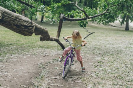 kid with bicycle standing near tree branch in park