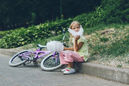 adorable kid with bicycle eating cotton candy in park