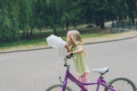 side view of adorable kid with bicycle eating cotton candy in park