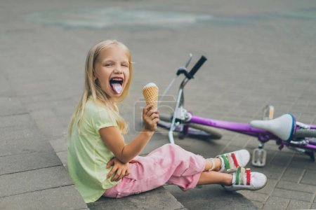 cute child with ice cream sticking tongue out while sitting on city steps alone