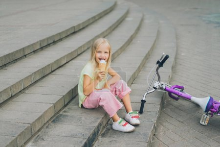 cute child eating ice cream while sitting on city steps near bicycle alone