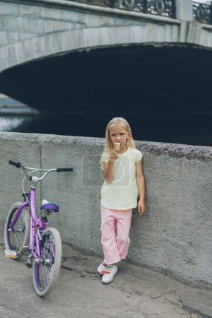 little child eating ice cream while standing near bicycle on street