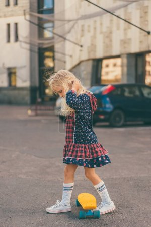 Photo for Side view of little adorable child riding on skateboard at urban street - Royalty Free Image