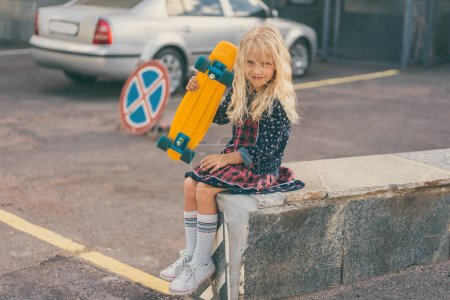 adorable smiling kid holding skateboard and sitting at urban street