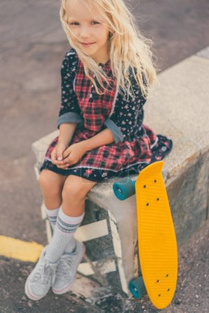 adorable smiling child sitting near skateboard and looking at camera at urban street