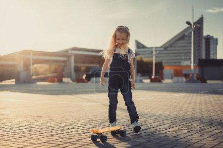 Photo pour Sourire adorable enfant debout avec planche à roulettes au stationnement - image libre de droit