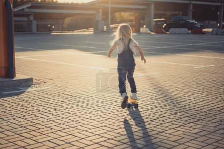 rear view of little kid riding on skateboard at parking lot