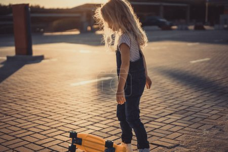 side view of little child standing near skateboard at parking lot
