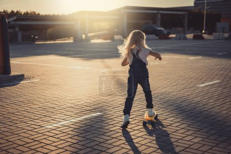 rear view of little kid riding on skateboard at parking lot with sunset behind