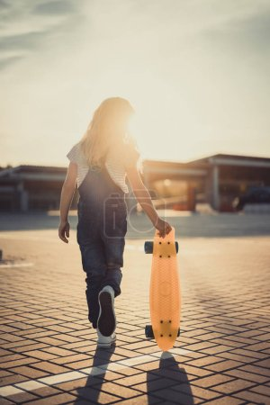 rear view of little kid walking with skateboard at parking lot with setting sun behind