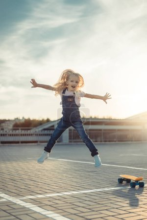 adorable little child jumping with wide arms near skateboard at parking lot