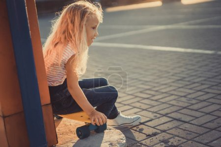 selective focus of smiling little child sitting on penny board at parking lot