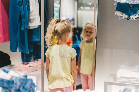 Photo for Rear view of smiling little kid looking at own reflection in mirror in shop - Royalty Free Image