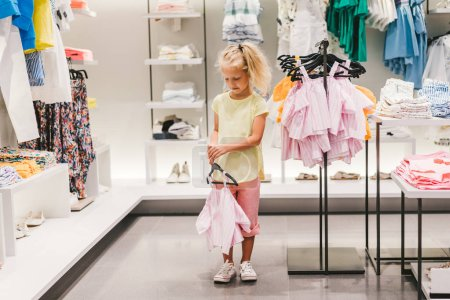 Photo for Front view of adorable little child holding hanger with shirt in shop - Royalty Free Image