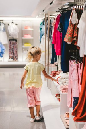 Photo for Rear view of little child choosing clothes in shop - Royalty Free Image
