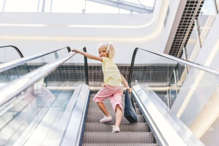 Photo for Low angle view of smiling little child with shopping bag in hand on escalator at mall - Royalty Free Image