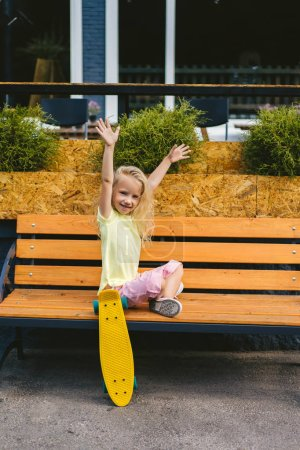 happy adorable child sitting with wide arms on bench near skateboard at street