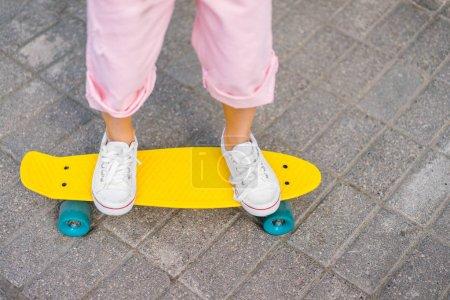 Photo pour Image recadrée de petit enfant à cheval sur la planche à roulettes au milieu urbain de la rue - image libre de droit