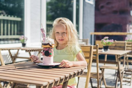 Photo for Selective focus of adorable little kid eating tasty dessert and looking at camera - Royalty Free Image