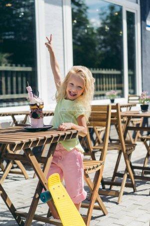 mise au point sélective d'enfant souriant, faisant le geste de paix à table avec délicieux dessert au café