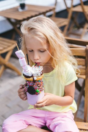 Photo for Selective focus of adorable little child with closed eyes eating delicious dessert in cafe - Royalty Free Image