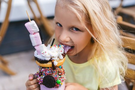 Photo for Portrait of adorable little child looking at camera and eating delicious dessert - Royalty Free Image