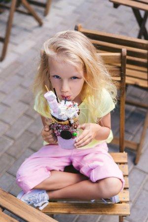 Photo pour Vue d'angle élevé d'adorable petit enfant manger délicieux dessert et regardant la caméra café - image libre de droit