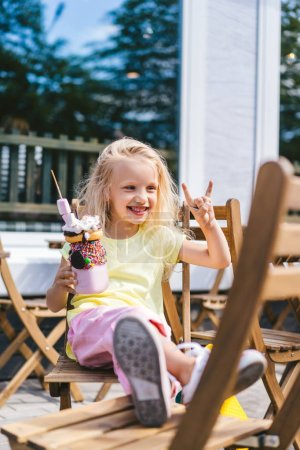 selective focus of happy adorable child doing rock gesture and holding delicious dessert in cafe