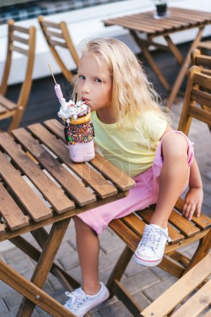 Photo for High angle view of adorable little child eating dessert and looking at camera at table in cafe - Royalty Free Image