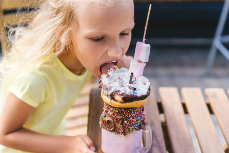Photo for Selective focus of adorable little child eating tasty dessert at table in cafe - Royalty Free Image