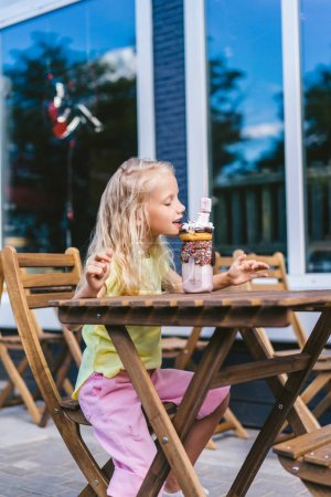 Photo for Selective focus of little child with closed eyes eating delicious dessert at table in cafe - Royalty Free Image