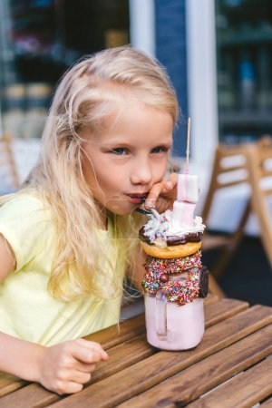 Photo for Portrait of happy little child eating dessert and looking away at table in cafe - Royalty Free Image
