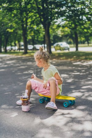 Photo for Side view of little child sitting on skateboard in front of dessert at street - Royalty Free Image