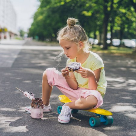 Photo for Side view of little child eating doughnut from dessert while sitting on skateboard at street - Royalty Free Image