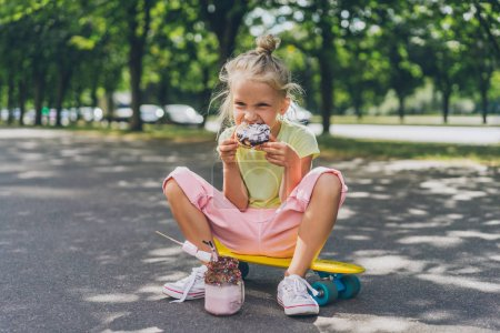Photo for Selective focus of little child eating doughnut from dessert while sitting on skateboard at street - Royalty Free Image