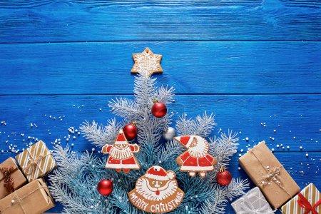 Photo pour Biscuits et cadeaux de pain d'épice de Noel sur un fond en bois bleu avec des décorations et des branches d'épinette. - image libre de droit