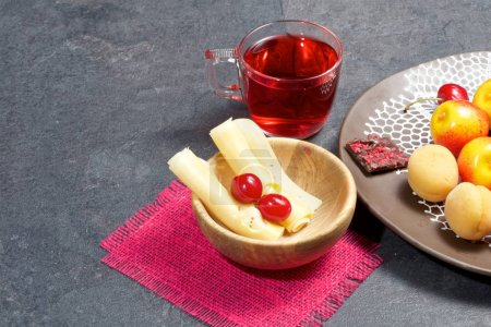 Photo pour On a dark wooden background - a mug with tea, a decorative dish, a wooden cup, strawberries, cherries, sweets, cookies. - image libre de droit