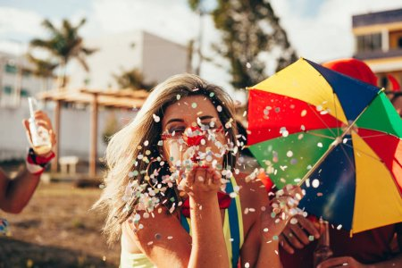 Photo for Brazilian Carnival. Young woman in costume enjoying the carnival party blowing confetti - Royalty Free Image