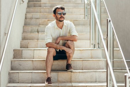 Photo for Portrait of man sitting on staircase in the street - Royalty Free Image