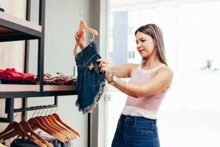 Photo for Young woman shopping in clothing store - Royalty Free Image