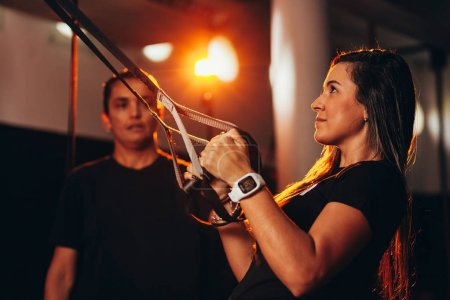 Young fitness woman training with trx fitness straps