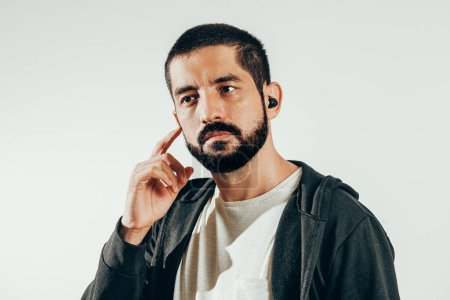 Photo for Young bearded man wearing sports clothes putting on wireless earphones. - Royalty Free Image