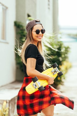 Photo for Young positive woman carrying skateboard in the city - Royalty Free Image