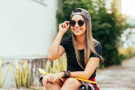 Photo for Young skateboarder wearing sunglasses and cap sitting on the sidewalk - Royalty Free Image