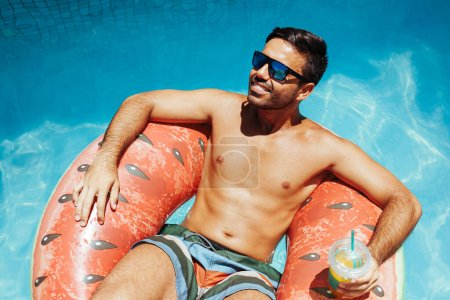 Photo for Handsome man relaxing alone on a float in the pool on a hot summer day - Royalty Free Image