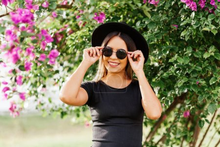 Photo for Portrait of young woman wearing sunglasses and fedora hat on a summer day - Royalty Free Image