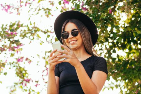 Photo for Hipster woman wearing sunglasses and fedora hat using cellphone. - Royalty Free Image