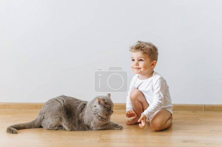 Photo for Cute little child in white bodysuit and grey british shorthair cat resting on floor at home - Royalty Free Image