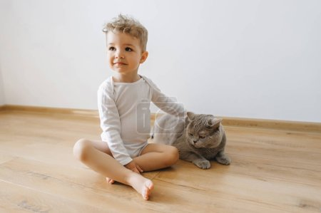 cute little child in white bodysuit and grey british shorthair cat at home